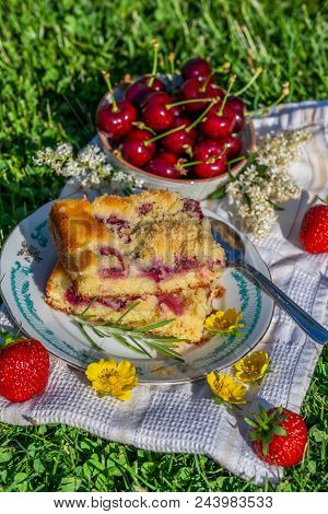 Portion Of Cherry Cake With Ripe Strawberries Around And Other Cherries In Bowl
