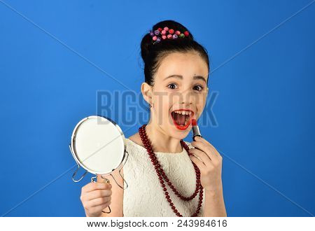 Childhood And Happiness. Childhood, Little Girl Pit Red Lipstick On Lips With Mirror