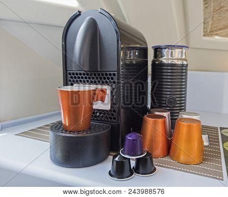 Closeup Still Life Of Espresso Coffee Maker Machine With Mug Cups And Capsule Pods