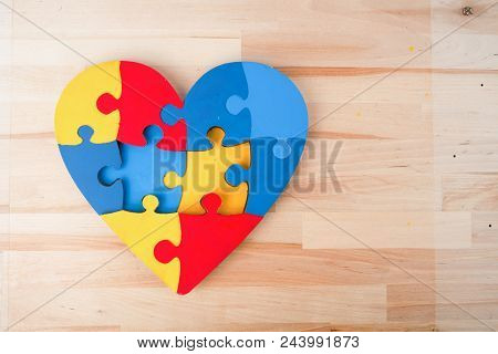 A Colorful Heart Made Of Symbolic Autism Puzzle Pieces On Wooden Background