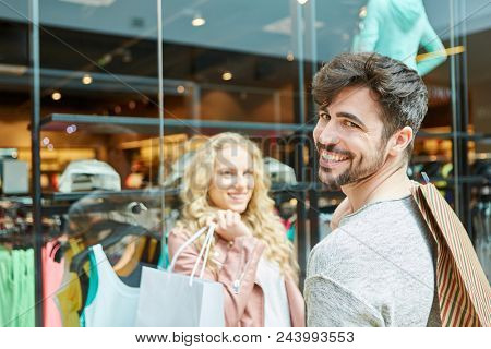 Happy young couple shopping for fashion in shopping mall
