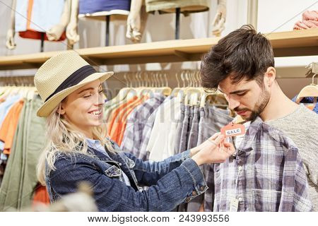 Young couple shopping for matching clothes in shopping mall