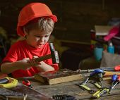 Child in helmet cute playing as builder or repairer, repairing or handcrafting. Toddler on busy face plays at home in workshop. Handcrafting concept. Kid boy hammering nail into wooden board. poster