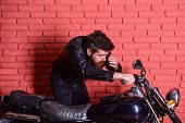 Masculinity concept. Man with beard, biker in leather jacket near motor bike in garage, brick wall background. Hipster, brutal biker on serious face in leather jacket looks into mirror of motorcycle. poster