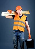Construction and woodworking concept. Carpenter, woodworker, labourer, builder on dreamy face carries wooden beams on shoulder. Man in helmet, hard hat holds toolbox and wooden beams, grey background. poster