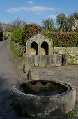 Very unusual well and trough in the village of Curbar. This was once the water supply for residents of this picturesque Peak District village poster