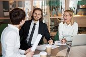 Smiling businesspeople laughing at partner joke during meeting in boardroom, colleagues having fun negotiating about business project, having friendly conversation discussing. Concept of partnership poster