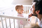 A small toddler girl standing in cot touching her fathers face at home. Paternity leave. poster