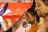 Thai man gilded Buddha statue on forehead with right hand. poster