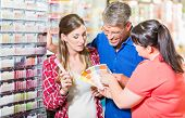 Home improvement store clerk counseling customers about choice of colour for wall paint poster