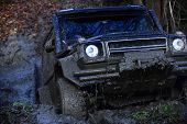 SUV covered with mud stuck in deep puddle. Extreme entertainment concept. Crossover overcomes obstacles on autumn day in forest. Black crossover driving through dirt with nature on background. poster