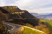 Curvy road in the mountains at the end of the pyrenes in France with the early morning sun lighting the village and the bridge in the valley nearby. poster