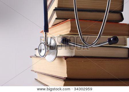 Stethoscope on pile of books isolated. Blue background