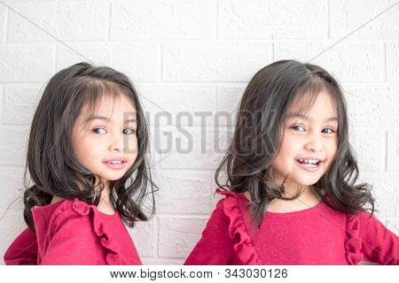An Identical Twin Girls Sisters Are Posing For The Camera. Happy Twin Sisters In Dresses Are Looking