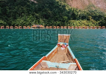 Wooden traditional thai longtail boat on Cheow Lan lake with raft houses in Khao Sok National Park, Thailand