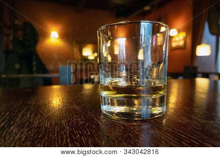 Drinking Whiskey In An Empty Bar. Golden Colour Alcohol Drink On Wooden Table In A Pub. Relaxing Aft