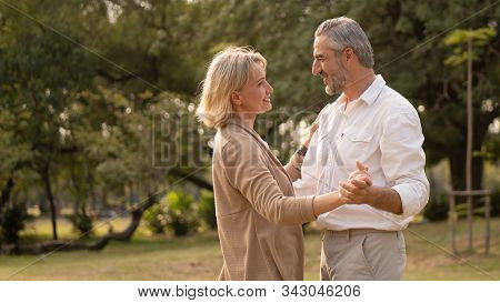 Senior Elegant Caucasian Couple Dancing Looking At Each Other Feeling Love And Cherish On Their Anni