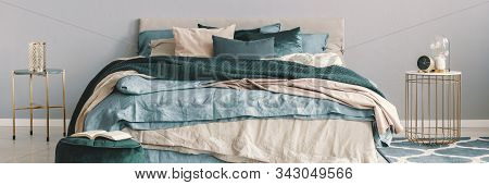 King Size Bed With Beige, Blue And Emerald Green Bedding Between Two Stylish Nightstands In Fashiona
