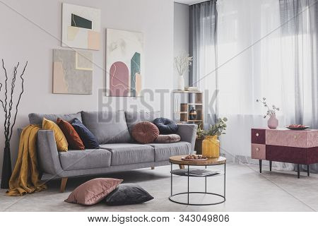 Real Photo Of Abstract Paintings Hanging On White Wall Above A Gray Sofa In A Living Room Interior W