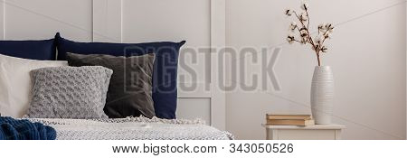 Cotton Flower In White Vase On Trendy Small Table In White Bedroom With Blue Bedding On Bed