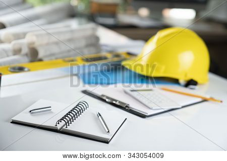 Contractor Office. Tool Kit Of The Contractor: Yellow Hardhat, Libella,  And Notebook On The White D