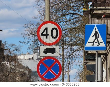 Cluster Of Road Signs: Pedestrian Crossing, No Waiting, Speed Limit 40 Km Per Hour, For Trucks Only,