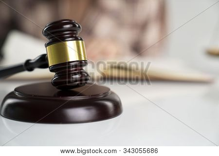 Young Female Lawyer During Work In Chamber. Gavel  On The White Table.
