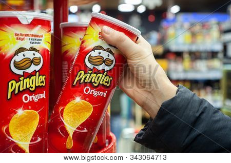 Minsk, Belarus - December 19, 2019: A Buyer Buys Pringles Chips At A Supermarket. Hand Hold A New Tu