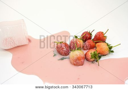 A Glass Of Water With Strawberry Juice Spilled Into Strawberries