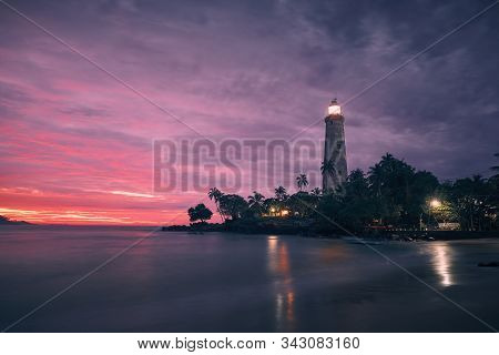 Illuminated Lighthouse In The Middle Of Palm Trees Against Dramatic Sky. South Coast Of Sri Lanka At