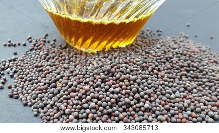 Mustered Seed And Oil In Bowl Isolated On Black Background