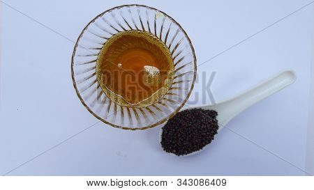 Mustered Oil In Bowl And Seed In Spoon Isolated On White Background