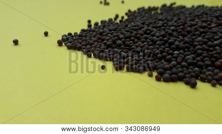 Mustered Seeds Isolated On Yellow Background Closeup