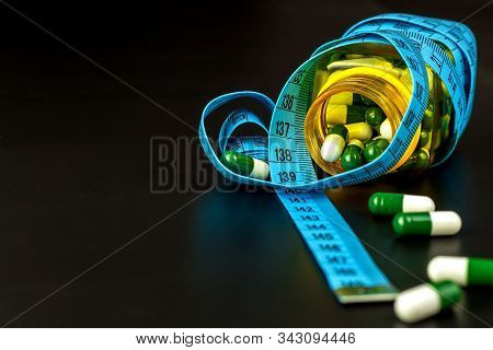 Pills With Measuring Tape. Weight Loss Concept. Obesity Medications. Healthy Life Style. Dangerous O