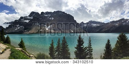 Snow-capped Mountains Rise Above A Turquoise Glacial Lake In Banff Canada; Panorama