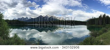 Panoramic Image Of A Reflection Of Mountains In The Canadian Rockies In A Glacial Lake Surrounded By