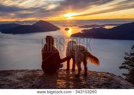 Adventurous Girl Hiking On Top Of A Mountain With A Dog During A Colorful Sunset. Taken On Tunnel Bl