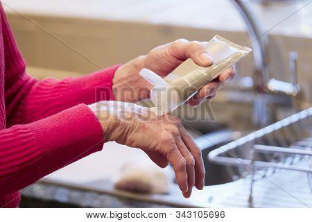 Elderly Senior Lady Applying Hand Cream To Old Wrinkled Cracked Dry Hands To Moisturise For Skin Car