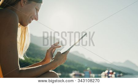 Low Angle View Of Smiling Young Woman Sitting On A Beach At Sunrise Browsing On Her Digital Tablet.