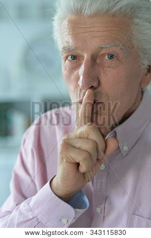 Senior Man With Finger On Lips Gesturing Silence
