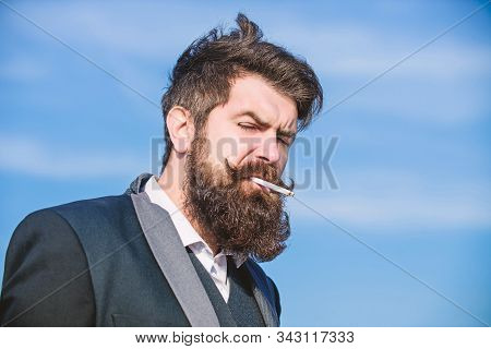 Truth About Smoking Pleasure And Nicotine Addiction. Bearded Hipster Smoking Cigarette Blue Sky Back