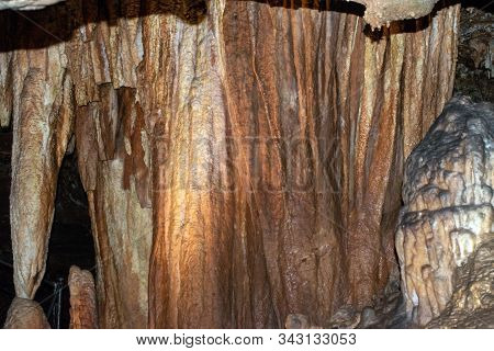 A Light Hits One Area Of This Cave Formation Making A Glow Amongst The Stalactites And Stalagmites.