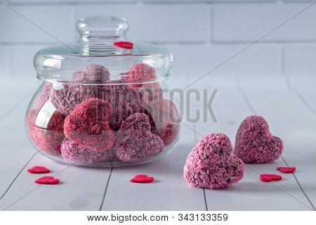 Heart Shaped Energy Bites For Valentine's Day On White Wooden Table