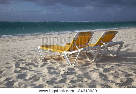 Two Empty Yellow Lounge Chairs On The Beach