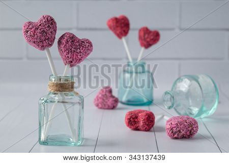 Composition With Heart Shaped Energy Bites For Valentine's Day On White Wooden Table