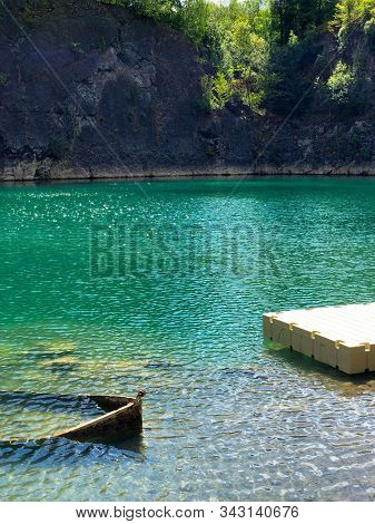 Abandoned Boat In Flooded Quarry With Blue Crystal Water. Diver Site With Fresh Blue And Clean Water