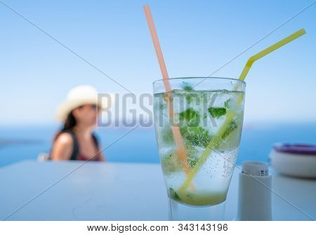 Fira, Santorini - August 8 2019; Cool Frosty Glass With Mojito Drink In Focus In Foreground With Per