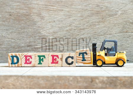 Toy Forklift Hold Letter Block T To Complete Word Defect On Wood Background