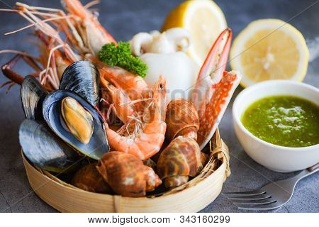 Fresh Shrimps Prawns Squid Mussels  Spotted Babylon Shellfish Crab And Seafood Sauce Lemon On Plate