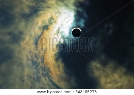 Terrifying Ominous Sky With A Solar Eclipse In The Middle. Dark Clouds Attack Light. Darkness Absorb